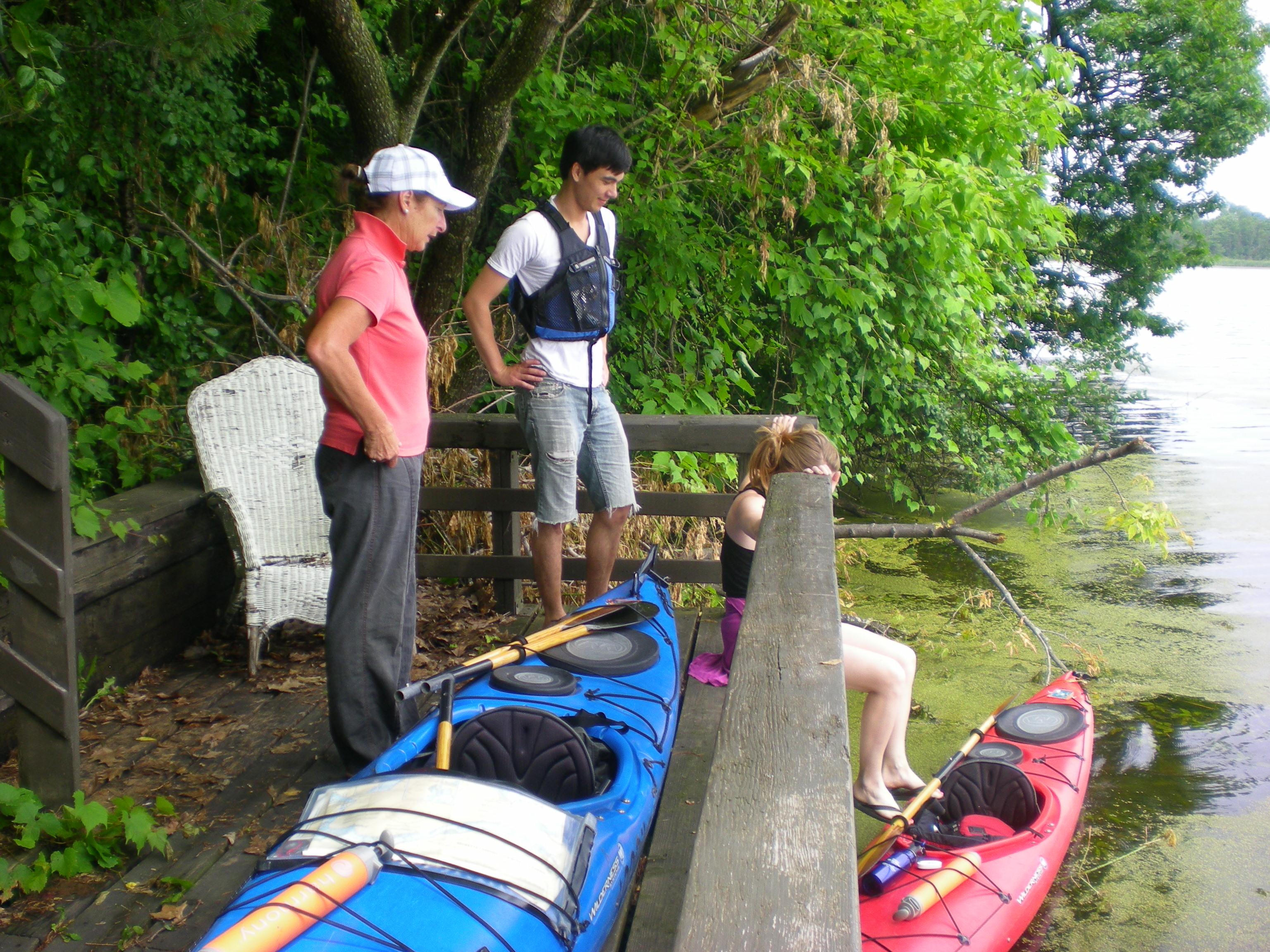 Image of people standing over kayaks.