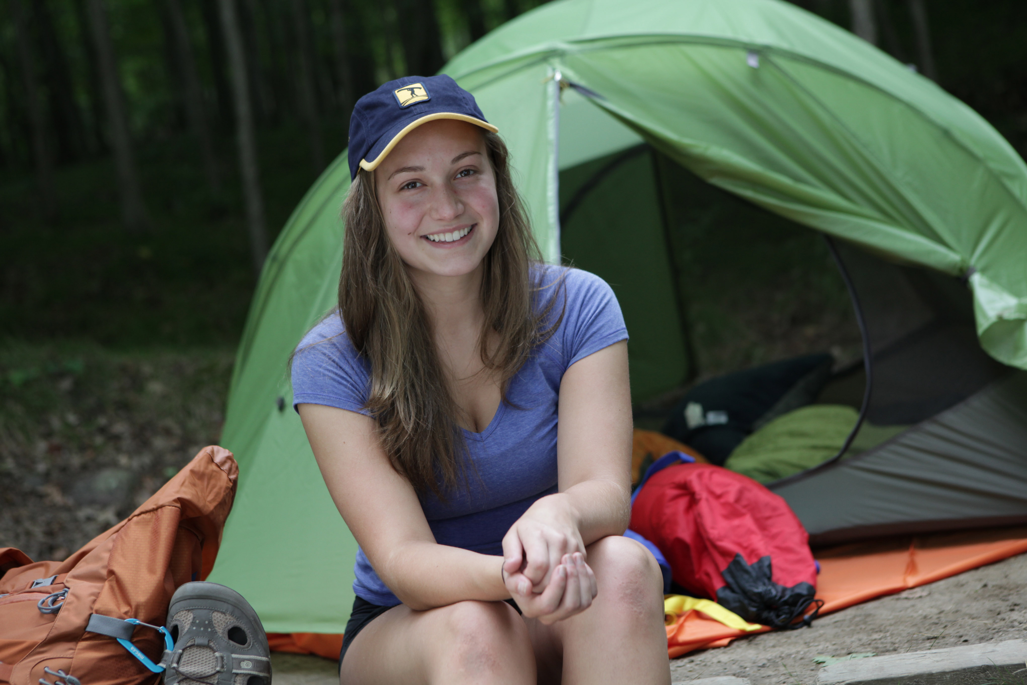 Image of a woman smiling infront of a tent.
