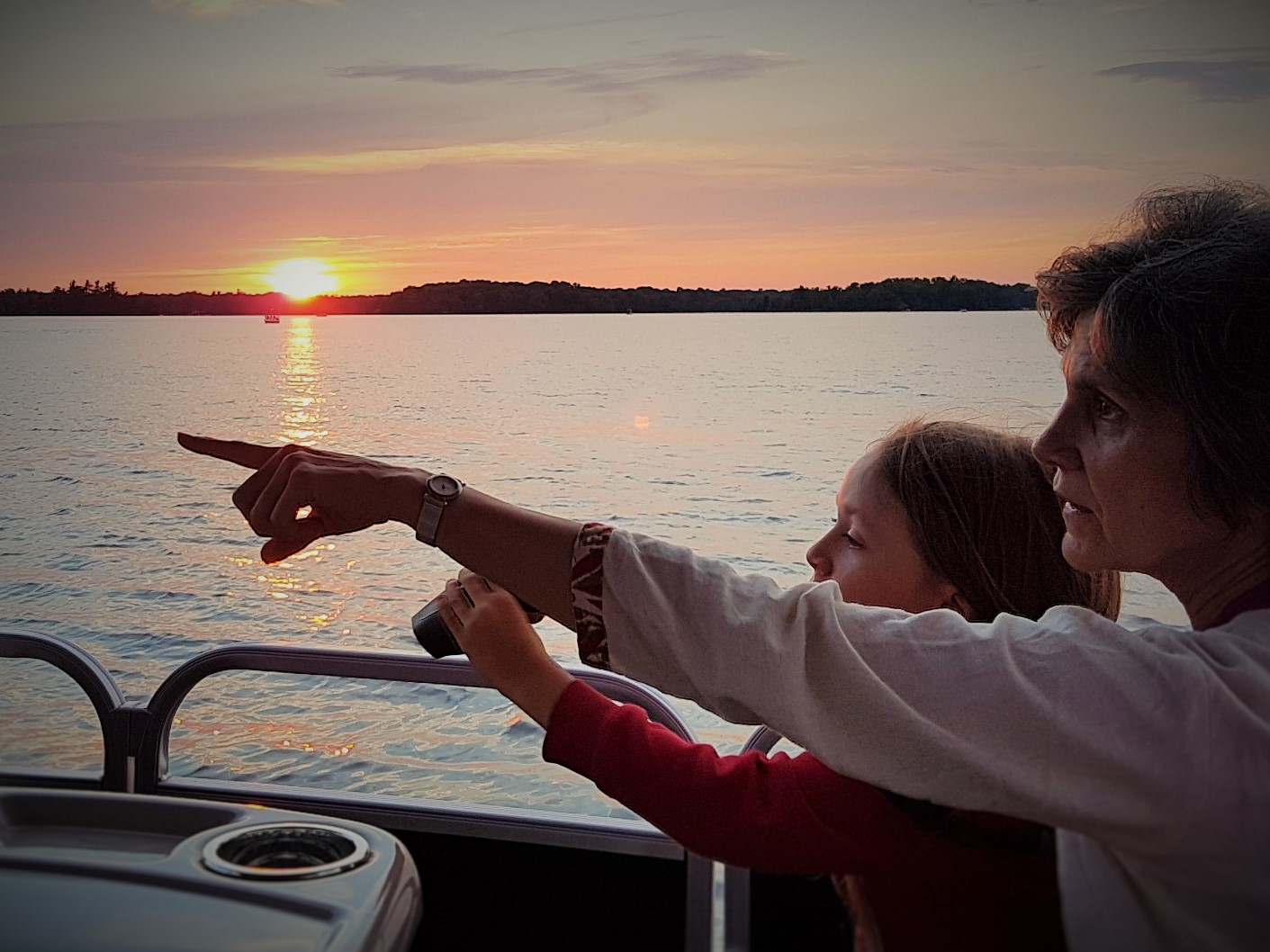 Image of people pointing on a boat with a sunset in the background.