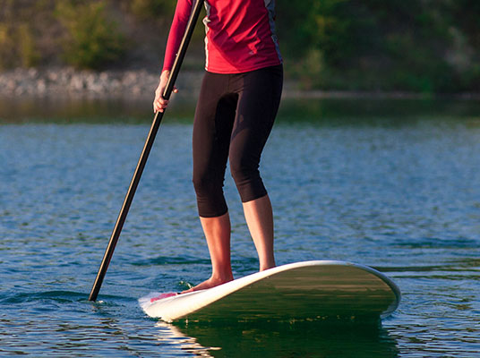 Women standing on a paddleboard.