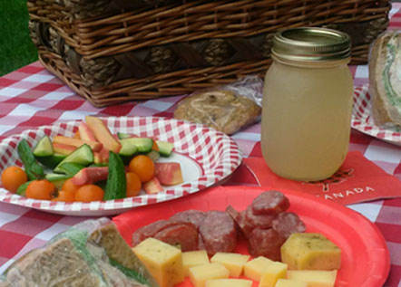 Image of an array of food on a picnic blanket.