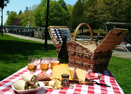 Image of a picnic basket with an array of food on top of a picnic blanket.